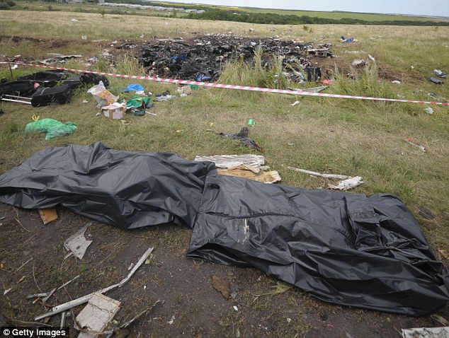 Discarded: Body bags containing the remains of MH17 passengers were seen dumped around the crash site for several days after the crash. Many of the bodies were decomposing in the summer heat