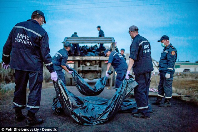 Undignified: Dozens of bodies of MH17 victims were seen being loaded on to a rubbish truck so they could be removed from the crash site and taken to a train station in Torez