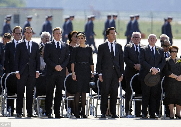 Respect: King Willem-Alexander (second left) Queen Maxima (third left) and Prime Minister Mark Rutte (third right) observe a minute of silence during a ceremony to mark the return of the first bodies of passengers and crew killed in the downing of Malaysia Airlines Flight MH17