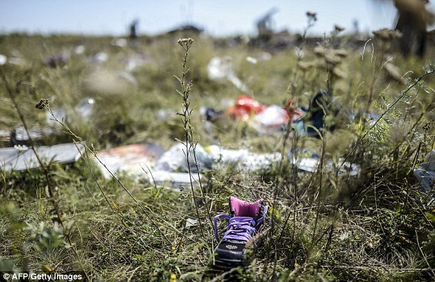 Tragic: A child's shoe is seen among the wreckage of MH17. A week after the disaster took place, the crash site is still littered with debris and, in some cases, body parts