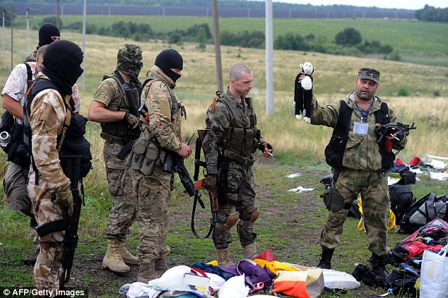 A pro-Russian militant holds up a stuffed animal as others look on at the site of the MH17 crash. 298 people were killed when the plane was apparently blasted out the sky by a surface to air missile