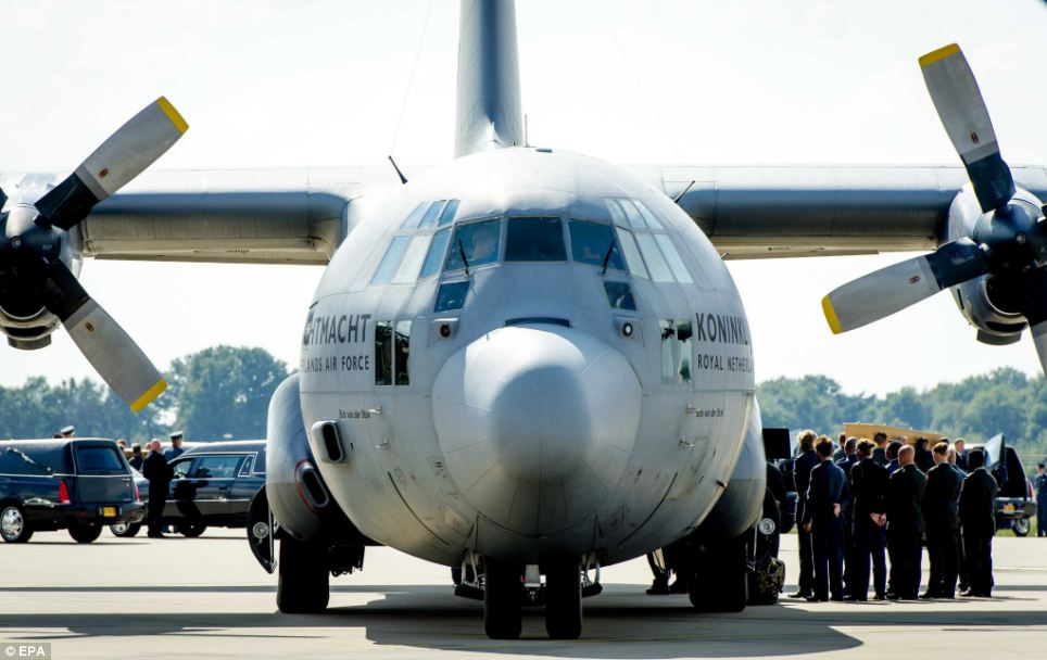 Hercules plane: Dutch military personnel are seen carrying a coffin containing the remains of the a MH17 victim away from the Dutch Air Force C-130 Hercules plane