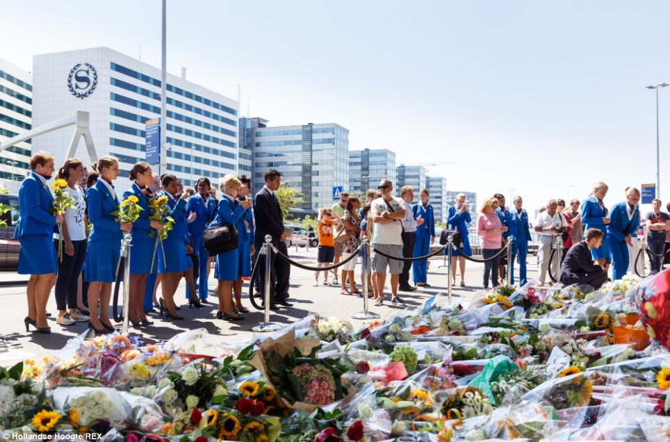 Mourning: Airline crew were among dozens of people to lay flowers for the victims of Mayalsia Airlines Flight MH17 in Eindhoven, the Netherlands, today