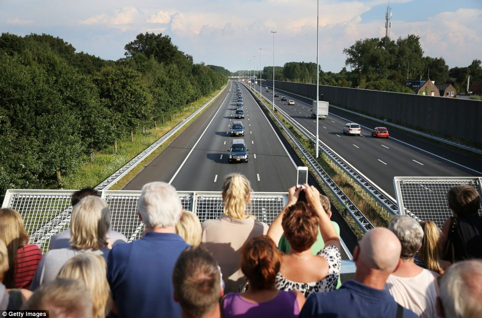 Procession: People watch from a bridge as a convoy of hearses carry bodies and remains from those killed on the Malaysian Airlines flight MH17 to Hilversum