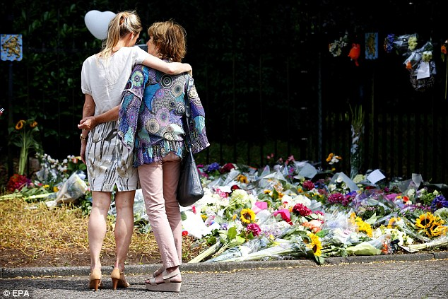 Mourning: Two women hug in front of a flower tribute at the entrance to the Korporaal van Oudheusdenkazerne, army barracks, in Hilversum, The Netherlands, where the bodies of the people killed in the Malaysia Airlines MH17 air crash in Ukraine will be identified