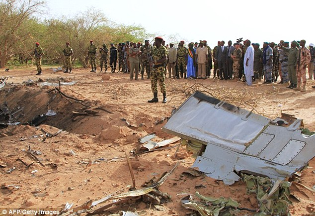 Wreckage: Soldiers from neighbouring Burkina Faso were today pictured standing over the plane's wreckage