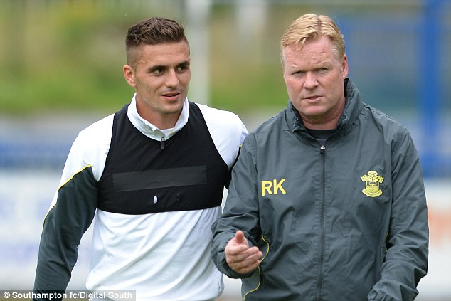 Making plans: Koeman and new wideman Dusan Tadic chat on the training field in Belgium