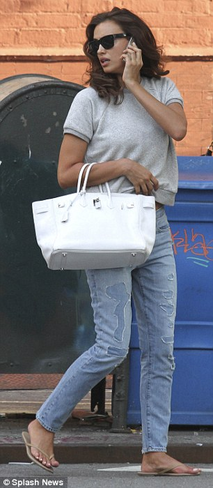 Show off: Irina donned a pair of loose fit straight leg jeans with a grey knit short sleeve sweater that she tucked up on one side