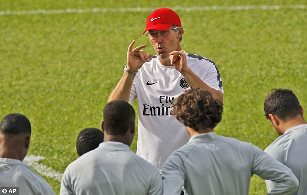 Holding court: Paris Saint Germain manager Laurent Black speaks to his players during training on Saturday