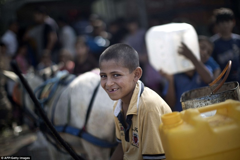 Suffering: A Palestinian child waits to collect drinking water in Jabalia in the northern Gaza Strip. At least three more Palestinians were killed this morning, medics said