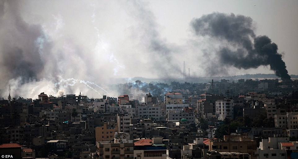 Carnage: Smoke rises after Israeli tanks shell the Al Shejaeiya neighbourhood during a military operation in Gaza City this morning, as the previous truce lay in tatters