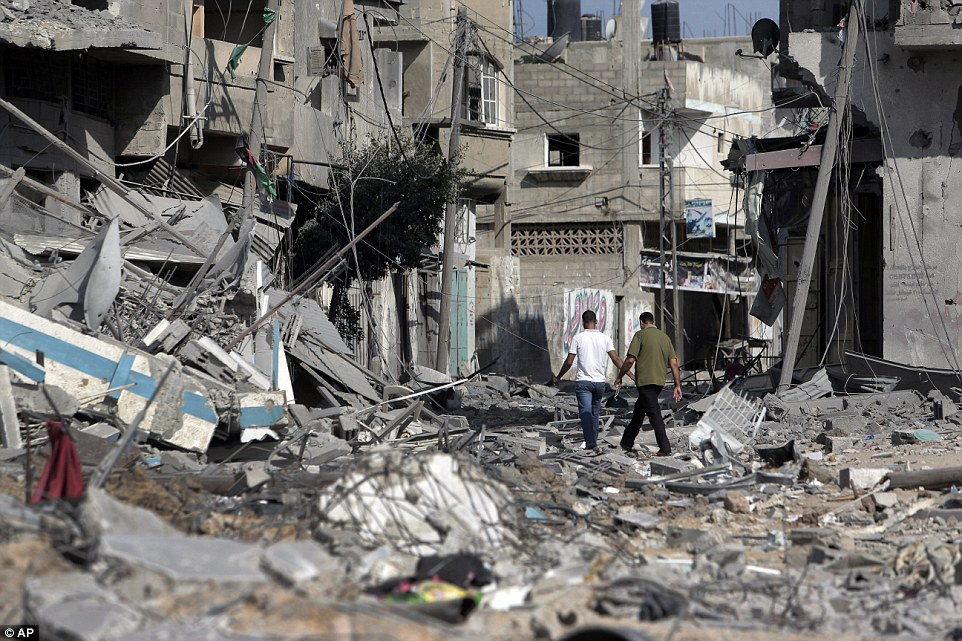 Aftermath: Despite bombings beginning again this morning, Palestinians still walked through the rubble of their homes to retrieve their belongings in Beit Hanoun, Gaza
