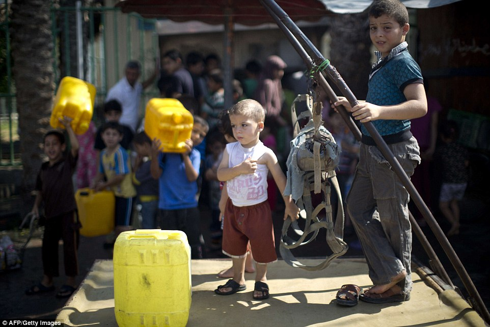 Taking stock: As debate continued over a ceasefire, Palestinian children made the trip to refill drinking water bottles at public tap in Jabalia in the northern Gaza Strip