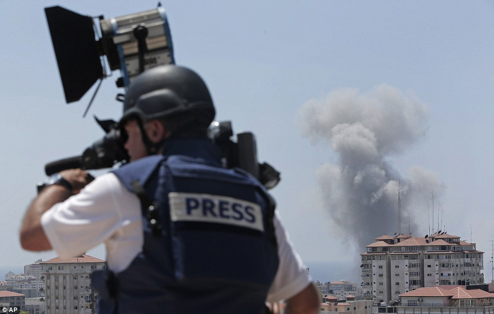 Eyes of the world: A news cameraman in a flak jacket films in Gaza after bombs began raining down again this morning. There have been international protests