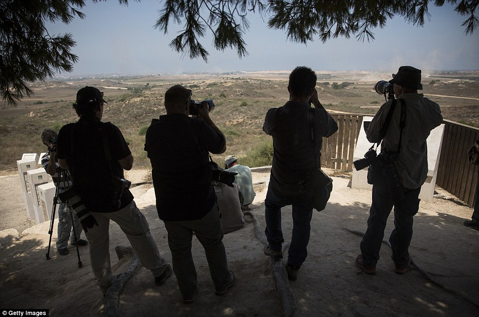Observers: Members of the media watch from Sderot, Israel. More than 1,060 Palestinians and 43 Israeli soldiers have been killed in the 20-day war, according to medics