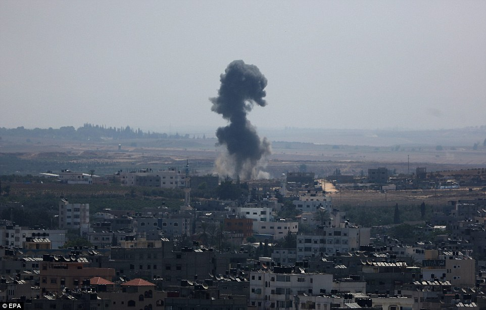 Strike: Smoke rising over Gaza City. As 2pm came and went, the sounds of rocket sirens in Israel and shelling in Gaza could still be heard by journalists and residents