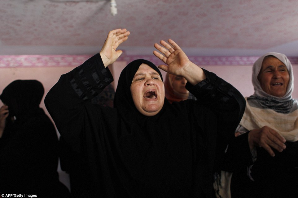 Turmoil: Relatives and friends mourn near the body of Hazem Abu Shamalah, who was killed in shelling after the Israeli military resumed its assault on Gaza