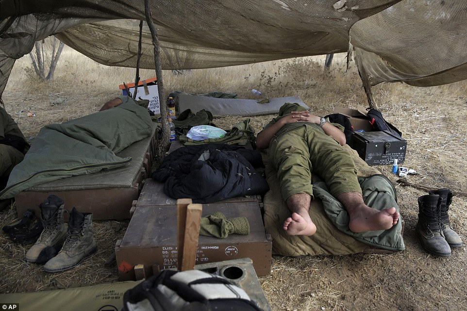 Relaxing: Israeli soldiers sleep in a tent near the border today. In the hours after a supposed ceasefire there was confusion as accusations flew on both sides