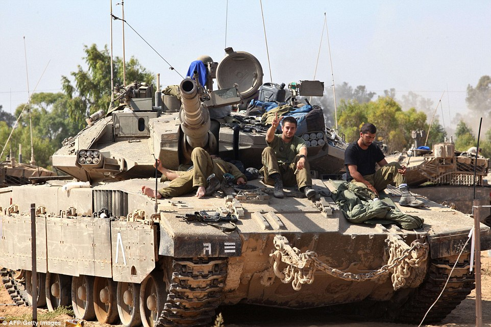Peace: Israeli soldiers make the famous V symbol on a tank. The conflict has killed more than 1,060 Palestinians and 43 Israeli soldiers in 20 days