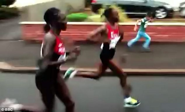 The little boy, who can be seen on the right running along the pavement, tried to keep up with the runners