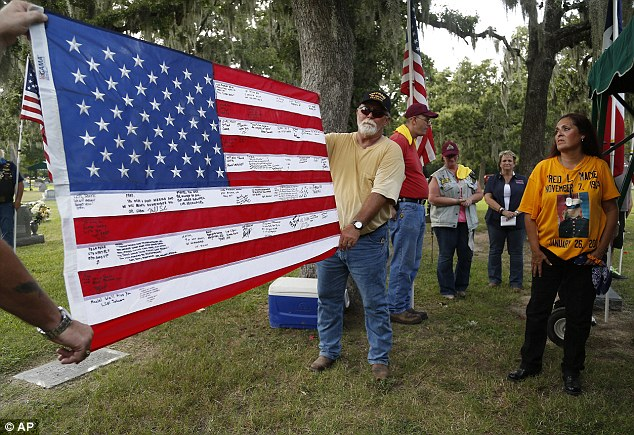 A flag that once belonged to Lance Cpl. Fred Maciel is unveiled at Calvary Hill Cemetery on Saturday in Humble, Texas