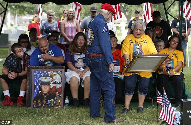 Hope Dorris gets a painting presented by Ken Pridgeon Sr. of her grandson Lance Cpl. Fred Maciel during the flag's unveiling