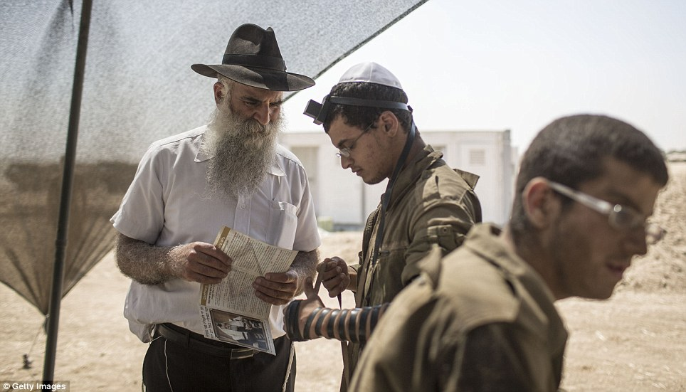 Israeli soldiers pray near the border. Forty-two Israeli soldiers and over 1,000 Palestinians have been killed as the Israeli operation 'Protective Edge' nears three weeks