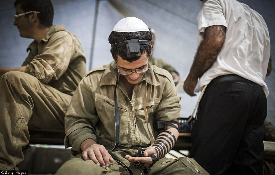 Israeli soldiers pray near the Israeli Gaza border as the 24 hour ceasefire began today. It did not last