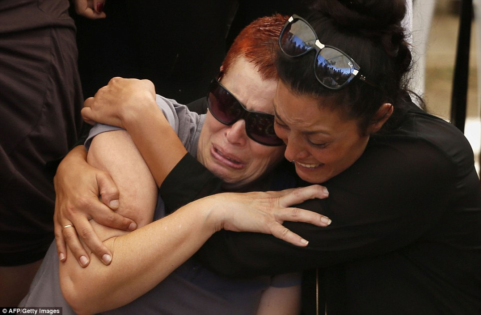 The mother (left) of 20-year-old Israeli St. Sgt. Amit Yeori mourns during his funeral at the Mount Herzl military cemetery in Jerusalem today