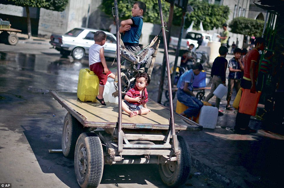 Palestinians wait to fill plastic bottles with drinking water at a public tap in Jabaliya in the northern Gaza Strip