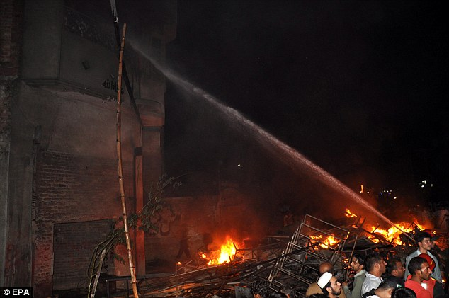 Firefighters try to extinguish fire at the houses of the religious minority group after a mob torched them, following accusations of blasphemy, in Gujranwala, Pakistan