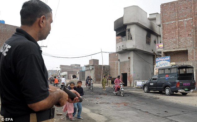 Police stand guard beside the houses of the religious minority group after they were torched