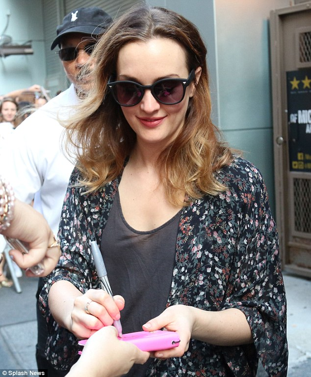 Here you go! The brunette beauty happily signed autographs for fans ass he exited the production