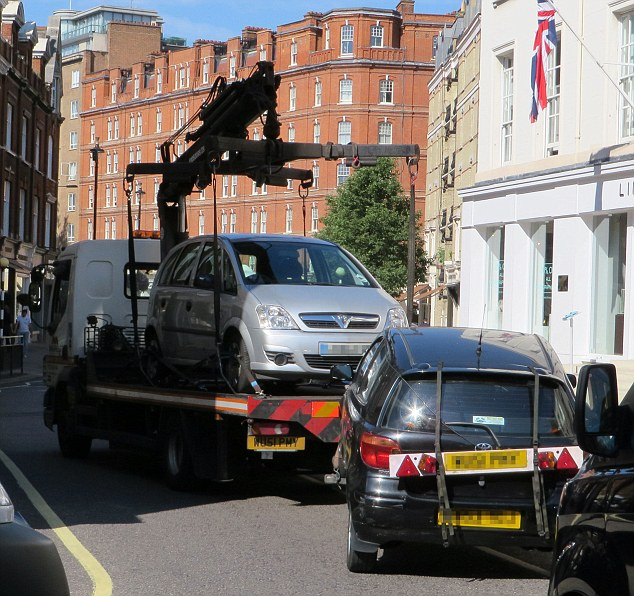 The woman ended up watching her black Toyota (front right) being towed away after the officers took action