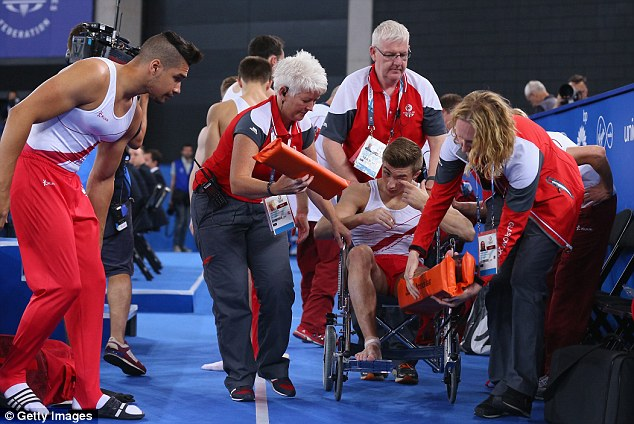 Down: Oldham is taken off the floor in a wheelchair after injuring his ankle during his vault routine