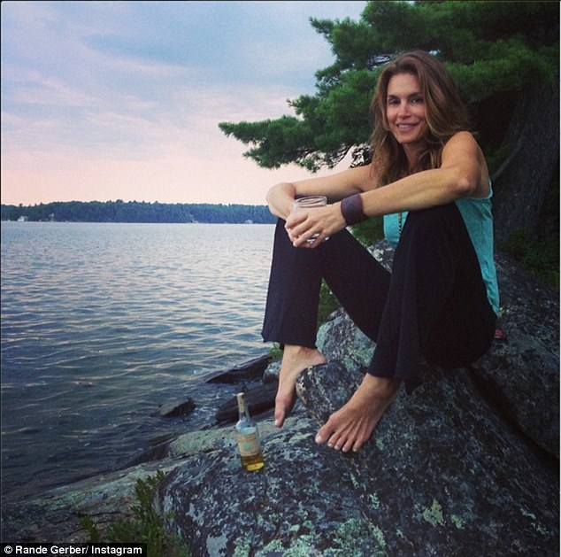 'On the rocks': Cindy Crawford was captured in all her naturally gorgeous glory during her idyllic family vacation on the lake