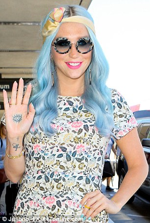 Kesha wears a colorful mini-dress before catching a flight at LAX with her former blue hair style