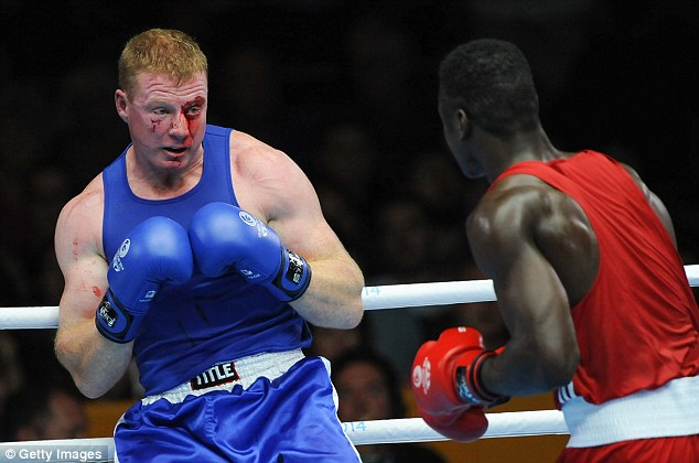 Bloody: Paul Schafer of South Africa (blue) and Efe Ajagba of Nigeria compete in the men's super-heavy boxing at the Scottish Exhibition Conference Centre in Glasgow today