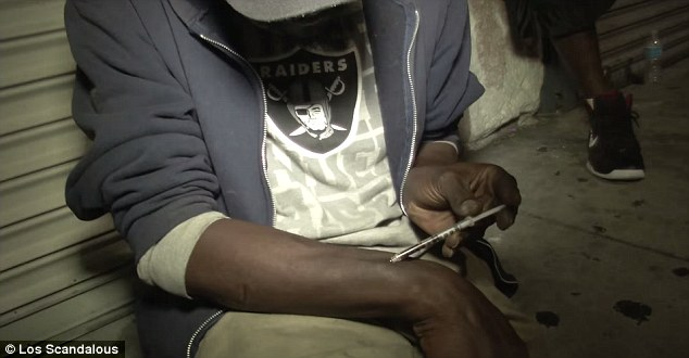 Addiction: A heroin user shoots up to get his fix while sat on the streets of Skid Row in Los Angeles