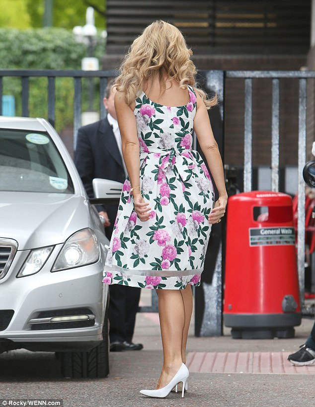 Looking leggy: Pairing some white court shoes with her ivory dress, the star showed off her bronzed pins to perfection