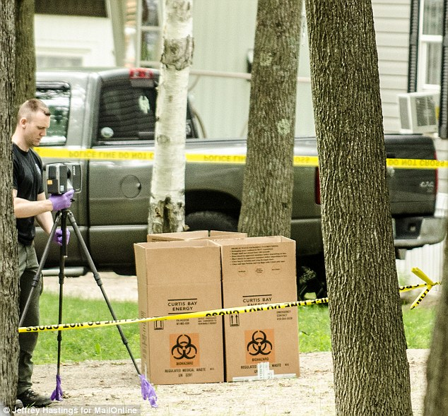 Documenting: An investigator takes pictures at Kibby's property on Wednesday with bio-hazard boxes seen in the background