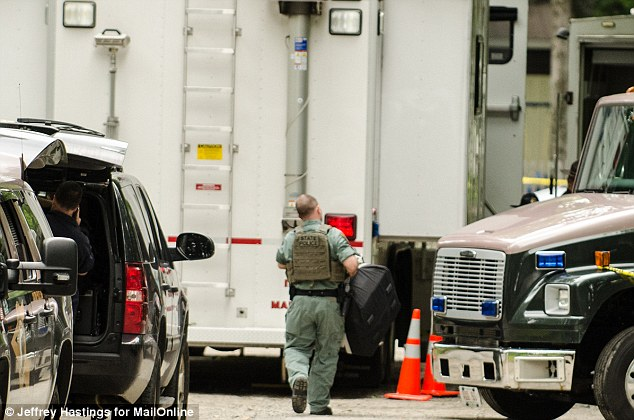 Safety: Investigators later donned bomb disposal gearr. Another police officer pictured on the suspect's property today