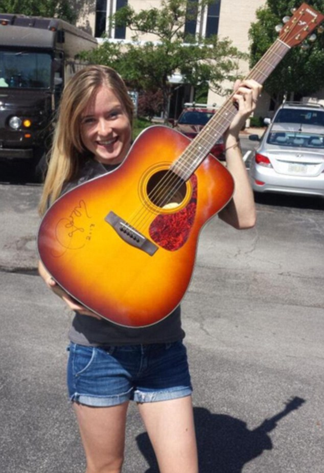 Soothed: Taylor Swift super fan Caitlyn was delighted after getting a reply from the singer on Instagram after she replied to the teen's message of love heartache, seen here with a signed guitar won in a radio contest