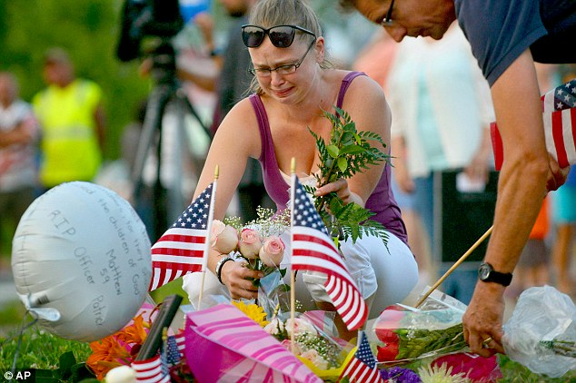 Gail Krull, a niece of Officer Scott Patrick, cries as she lays a bouquet of roses on a makeshift memorial during a candlelight vigil at the location where Patrick was killed