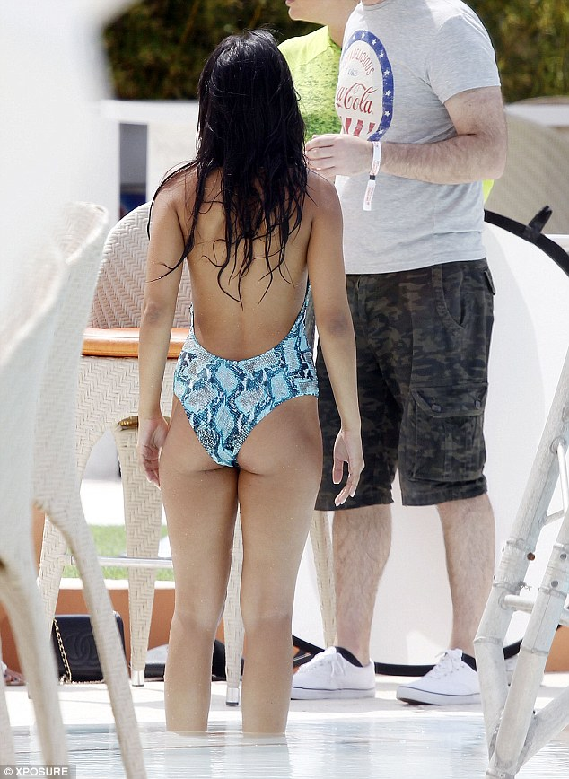 Showing off her assets: Jasmin wore her dark hair down as she took a dip in the pool