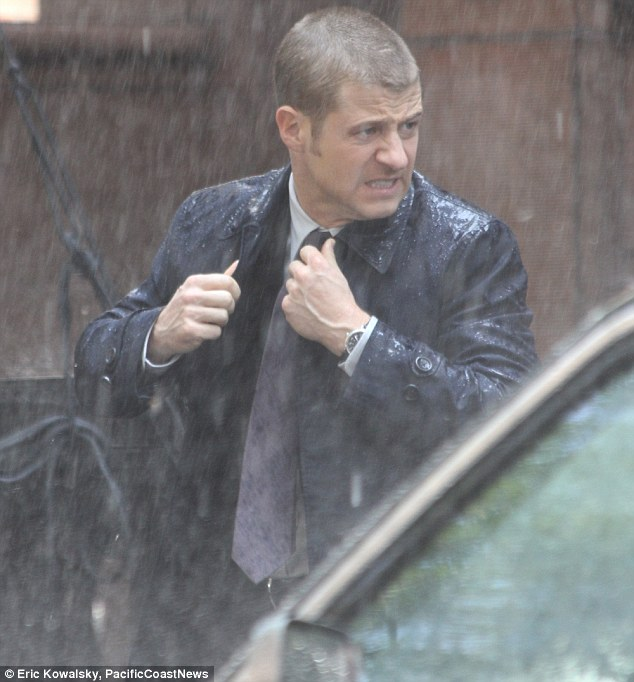 Here comes the rain again: The former OC hunk was getting soaked to the skin as he dashed aroud
