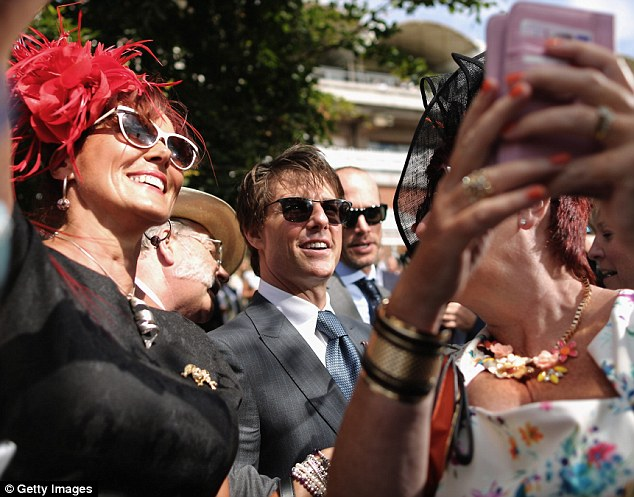 Point and click: The Hollywood actor gets his smile ready as he prepares to take a selfie with fans