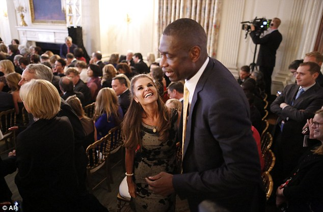 Former NBA star Dikembe Mutombo talks with Maria Shriver before singer Katy Perry performs at the event