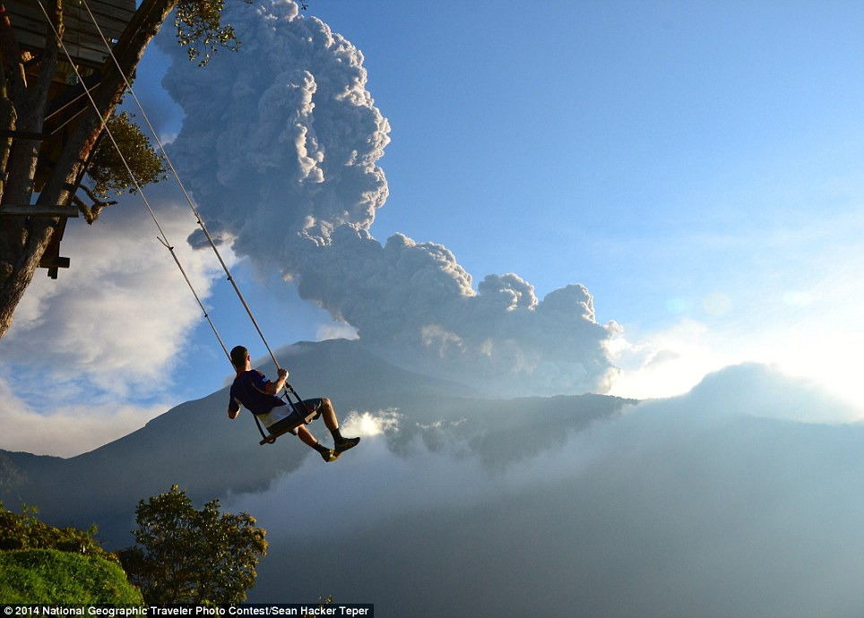 End of the World: This photo, taken at the 'end of the world' swing in Banos, Ecuador, captures a man on the swing overlooking an erupting Mt. Tungurahua. The eruption took place on February 1st, 2014. Minutes after the photo was taken, we had to evacuate the area because of an incoming ash cloud. Location: Banos, Ecuador (photo and caption by Sean Hacker Teper)