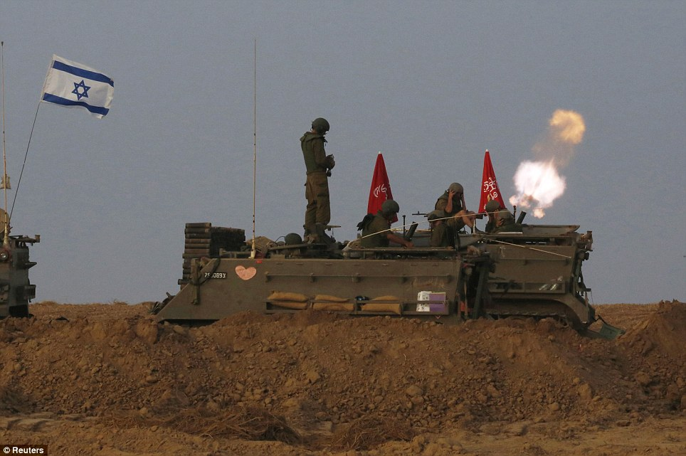 Onslaught: Israeli soldiers stand on an armoured personnel carrier outside the Gaza Strip as they fire mortar shell towards Gaza before the ceasefire was due to begin